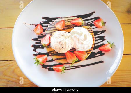Erdbeere Pfannkuchen Chocolate Chip Eis/Dessert frische Erdbeeren Obst auf Pfannkuchen mit Vanilleeis und Sahne gießen c - Stockfoto