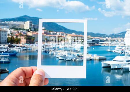 Nahaufnahme eines jungen kaukasischen Mann mit einem weißen Rahmen in seine Hand, am Hafen von Ajaccio, Simulation eines Instant Foto - Stockfoto
