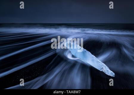 Meer driftet in um die Eisberge und das Gletschereis, die am Strand auf dem schwarzen Sand am Gletschersee Jökulsárlón, Island gefegt wird Stockfoto