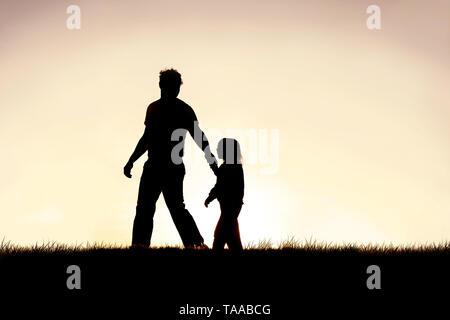 Die Silhouette eines jungen christlichen Vater leitet seine junge Kind von der Hand, wie Sie außerhalb bei Sonnenuntergang spazieren. - Stockfoto