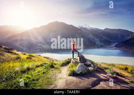 Touristische Frau mit Hut genießen Sie den Sonnenaufgang über dem See im Berg - Stockfoto