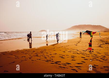 Atmosphärische Erfassung von Silhouetten, die spielen und Fliegen mit einem Drachen in schönen Sandstrand Golden Beach in Karpasia, Zypern - Stockfoto