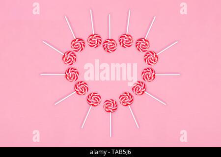 Herz aus Lollypop Bonbons auf rosa Hintergrund, kopieren. Süße Kindheit Konzept. Valentinstag Grusskarten. Flach. - Stockfoto