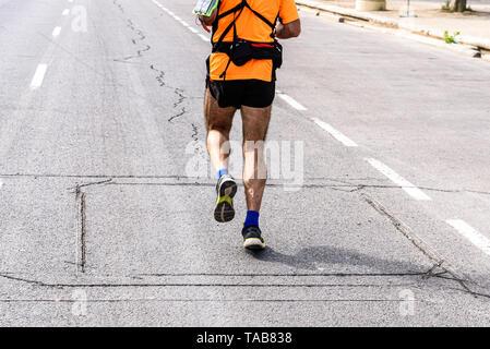 Ein reifer Mann Runner mit Fanny Pack Sport ausgestattet seine Beine zu trainieren, die auf dem Asphalt in der Sonne. - Stockfoto