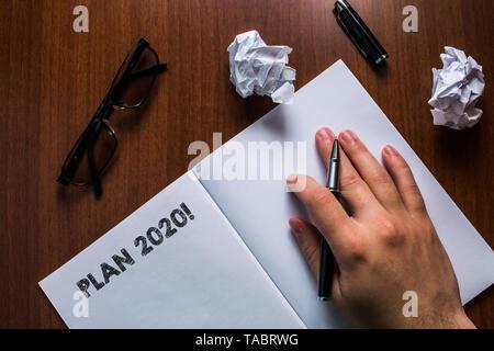Schreiben Hinweis Übersicht Plan 2020. Business Konzept für detaillierte Vorschlag für zu tun oder etwas zu erreichen, im nächsten Jahr Mann Hand pen open Notebook r - Stockfoto