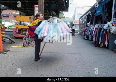 Eine lateinamerikanische Frau verkauf taschen von Zuckerwatte unter der erhöhten u-bahn in Jackson Heights, Queens, New York City. - Stockfoto
