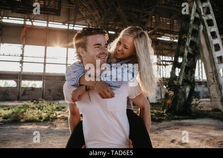 Glückliche junge Mann, Freundin ein piggyback Ride in einer alten Halle