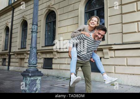 Glücklich, Mann, Frau, Huckepack Fahrt auf Asphalt in der Stadt - Stockfoto