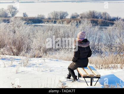 Eine junge Frau, die in den Strahlen der aufgehenden Sonne im Winter die Morgendämmerung am Ufer des südlichen Bug Fluss grüßt, sitzt auf einer Holzbank und schaut in den d - Stockfoto