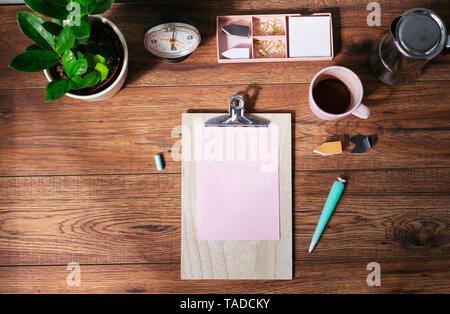 Clip Board mit leeren rosa Papier, Kaffeebecher und andere Utensilien auf dem Schreibtisch im Büro zu Hause, Ansicht von oben - Stockfoto