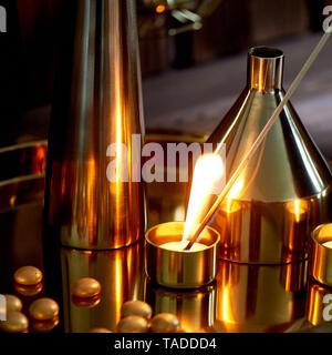 Hand leuchtet eine Kerze mit einer langen Match mit einer hellen Flamme. Die warmen goldenen Gamma. Abend Komfort. Viele Vasen in verschiedenen Formen von gold metall. - Stockfoto