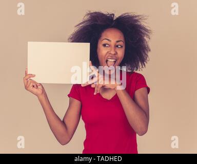 Lustig und attraktive junge afrikanische amerikanische weibliche angezeigt und zeigen auf Blank Board mit Kopie Platz für Text. Heiter gemischt Race woman holding Bla - Stockfoto