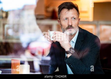 Portrait von Reifen Geschäftsmann mit Tasse Kaffee in einem Cafe - Stockfoto