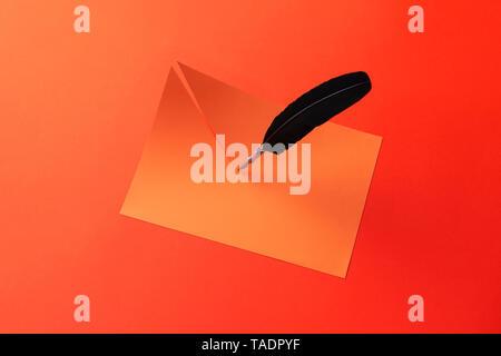 Federkiel schneiden das Papier zur Hälfte über den roten Hintergrund - Stockfoto