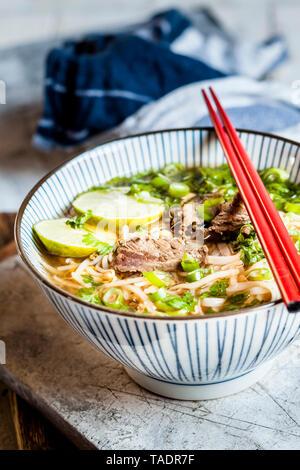 Schüssel mit vietnamesischen Pho mit Reis Nudeln, Mungbohnen, cilantro, Frühlingszwiebeln und Limetten - Stockfoto