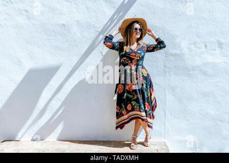 Spanien, Cadiz, Vejer de la Frontera, modische Frau mit Strohhut stand vor der weißen Wand Stockfoto