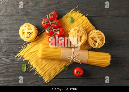Zusammensetzung mit Pasta, Tomaten und Basilikum auf hölzernen Hintergrund, Platz für Text und Ansicht von oben