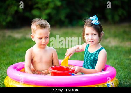 Thema kindheit Sommerspiele im Hof. Kaukasische Bruder und Schwester spielen Kunststoff Spielzeug Eimer im Wasser sitzen, aufblasbare runde Kinder- - Stockfoto