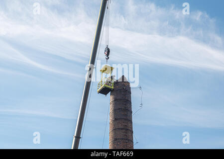2 Männer in einem Korb hängen von einem riesigen Kran, sorgfältig entfernen einer Fabrik Schornstein - Stockfoto