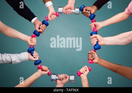 Gruppe von Menschen die Hand, runde Form mit bunten Hanteln vor grünem Hintergrund - Stockfoto