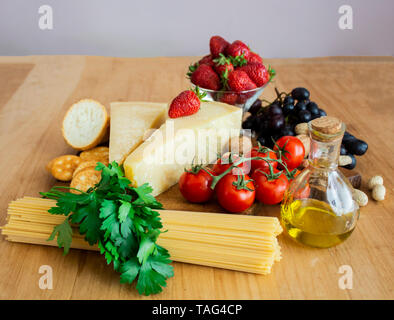 Spaghetti und Pasta auf dem hölzernen Hintergrund. Das Konzept des Kochens. Pasta, Tomaten, Käse, Minze und Erdbeeren. Für text - Stockfoto