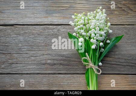 Maiglöckchen auf Holz- Hintergrund. Ansicht von oben. - Stockfoto
