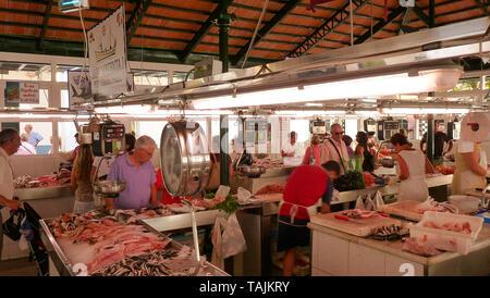 Blick auf den Fischmarkt in Ciutadella de Menorca, mit verschiedenen bunten Fisch, der für den Verkauf in den Vordergrund und touristische Kunden - Stockfoto