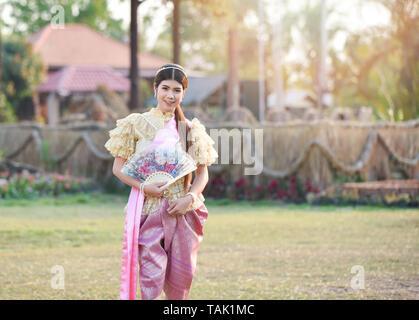Asien Frau Thai Style dress/Portrait von schönen jungen Mädchen lächelnd Thailand Tracht tragen mit Papier Lüfter in der Hand - Stockfoto
