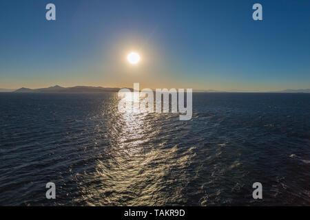 Reflexionen der untergehenden Sonne über dem Meer mit Schiffen und der Insel Egina im Hintergrund, Griechenland - Stockfoto