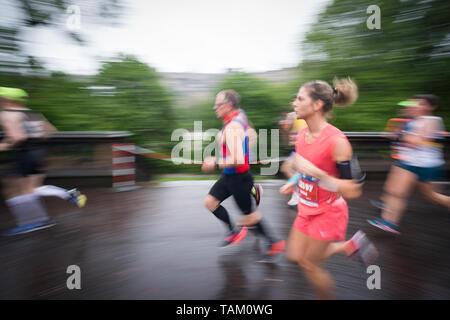 Wettbewerber, die sich an der 2019 in Edinburgh Marathon Festival Halbmarathon laufen durch die Princes Street Gardens im Regen. - Stockfoto