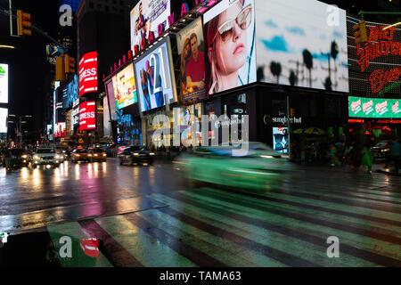 Der Times Square mit beleuchtete Werbetafeln in der Nacht im Regen - New York City, New York - Stockfoto