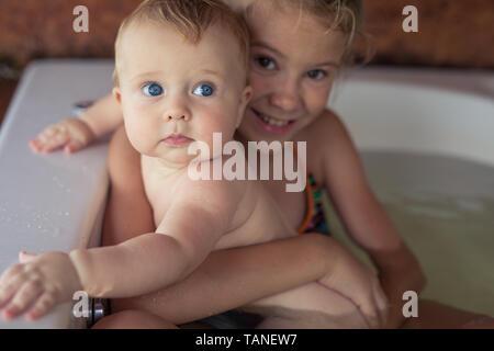 Zwei glückliche kleine Kinder in der Badewanne am Tag spielen. Kinder Spaß im Freien. Konzept der Kinder im Urlaub und freundliche Familie. - Stockfoto