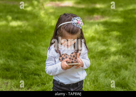 Adorable vier Jahre alt, süße kleine Mädchen in legere Kleidung hält und Texte Handy lächelnd an outdoor in Park - Stockfoto
