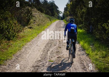Reife weibliche Radfahrer reiten durch Wald in Dänemark. - Stockfoto