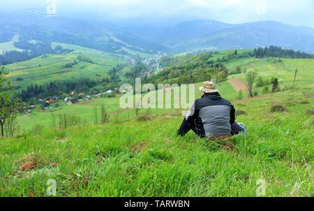 Ein einsamer Reisender auf dem Gras sitzt auf einem Hügel und blickt auf die malerische Landschaft der Karpaten und das Dorf im Tal, s - Stockfoto