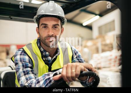 Porträt eines lächelnden Gabelstapler Fahrer trägt einen Schutzhelm und Weste während der Arbeit am Boden ein Teppich Lager - Stockfoto