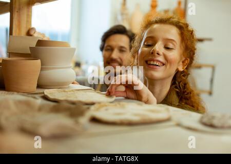 Prüfen Beispiele. Lachen schöne Mädchen in ungewöhnlichen ton Stücke interessiert während des Aufenthaltes in der Werkstatt - Stockfoto