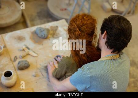 In intensiven Resin. Romantische junge Paare leidenschaftlich Umarmen während ungewöhnliches Hobby in der Werkstatt - Stockfoto