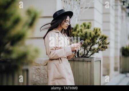 Junge gemischte Frau mobile Mobiltelefon und lächelnd im städtischen Hintergrund. Junge Mädchen legere Kleidung Stockfoto