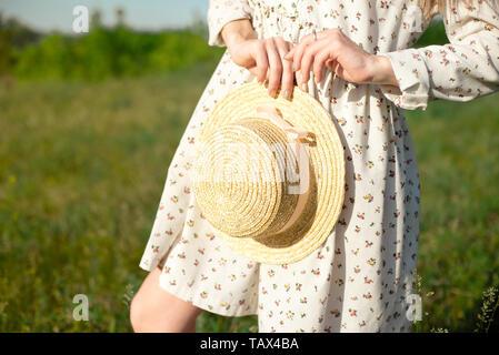 Close-up Portrait eines glücklichen und sanfte schöne Brünette Mädchen in einem Strohhut mit einem Hut in der Hand in einem Feld von grünem Gras und Hi steht. - Stockfoto