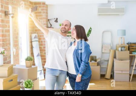 Junges Paar, ein Foto Foto mit Smartphone im neuen Zuhause und lächelt glücklich für Umzug in neue Wohnung - Stockfoto