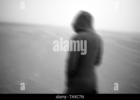 Eine Frau trägt eine Haube in der Öde kalte leere Landschaft braving zub Null Temperaturen - Stockfoto