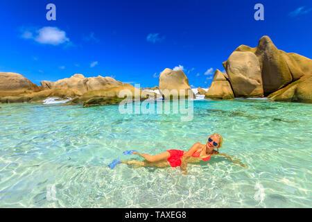 La Digue, Anse Marron, Schwimmbad. Attraktive Frau im Bikini liegen auf kristallklarem Wasser der natürlichen Pool an der Anse Marron von riesigen Felsen geschützt - Stockfoto
