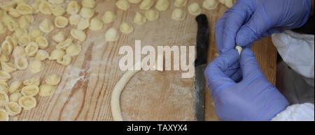 Frau Koch mit blauen Handschuhe bei der Zubereitung von frischem italienischen Pasta Orecchiette genannt ein typisches Gericht der Region Apulien - Stockfoto
