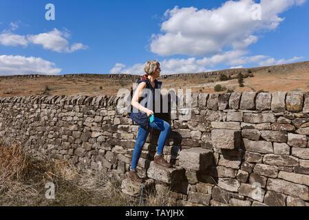 Ein Wanderer Frau überquert einen Stil auf der Hadrians Wall Spaziergang in Derbyshire Landschaft - Stockfoto