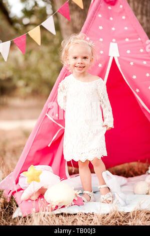Lächelnden Mädchen 3-4 Jahre alten Spielen in der Wiese im Freien. Tragen elegantes weißes Kleid. Kindheit. Sommer. - Stockfoto