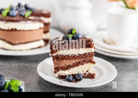 Die belgische Schokolade 2-in-1-Torte. Schichten von feuchten choco Schwamm, Vanillecreme und nachsichtige dunkle Schokoladenmousse glasiert mit reichen dunklen Schokolade sauc - Stockfoto