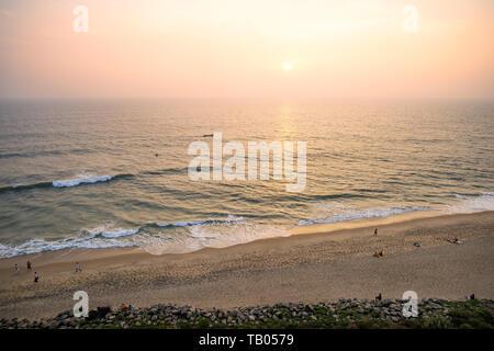 Ansicht von oben, einen atemberaubenden Blick auf einen wunderschönen tropischen Strand mit Menschen Sonnenbaden und genießen einen wunderschönen Sonnenuntergang. Cochin, Kerala, Indien. - Stockfoto