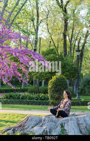 Lifestyle Konzept. Frau mittleren Alters meditieren in einem Park im Freien auf dem Baumstumpf. - Stockfoto