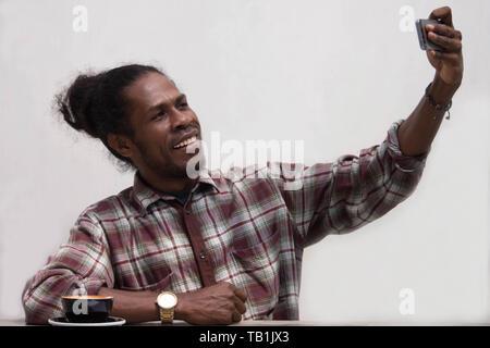 Junge schwarze Mann selfie und lächelnd in die Kamera, Papua junger Mann Lächeln, während selfie, Papua Mann mit Smartphone und unter selfie - Stockfoto